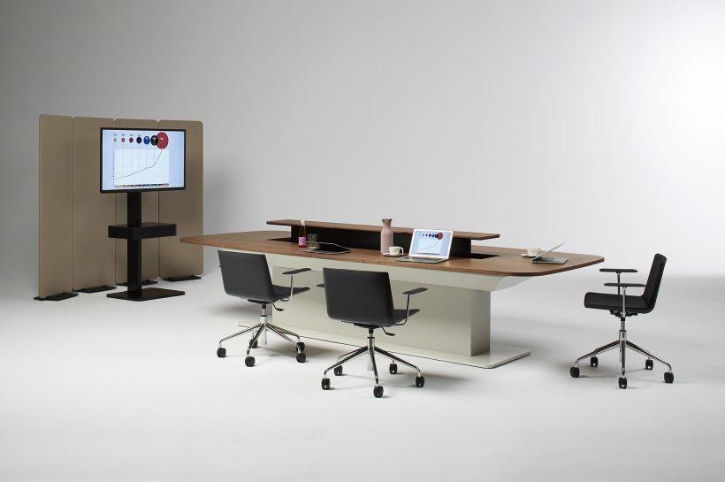 Una mesa rodeada de sillas y de fondo un televisor espacio perfecto para una videoconferencia